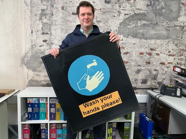 Richard Mayne of Footfall displaying a new rubber hand wash message mat